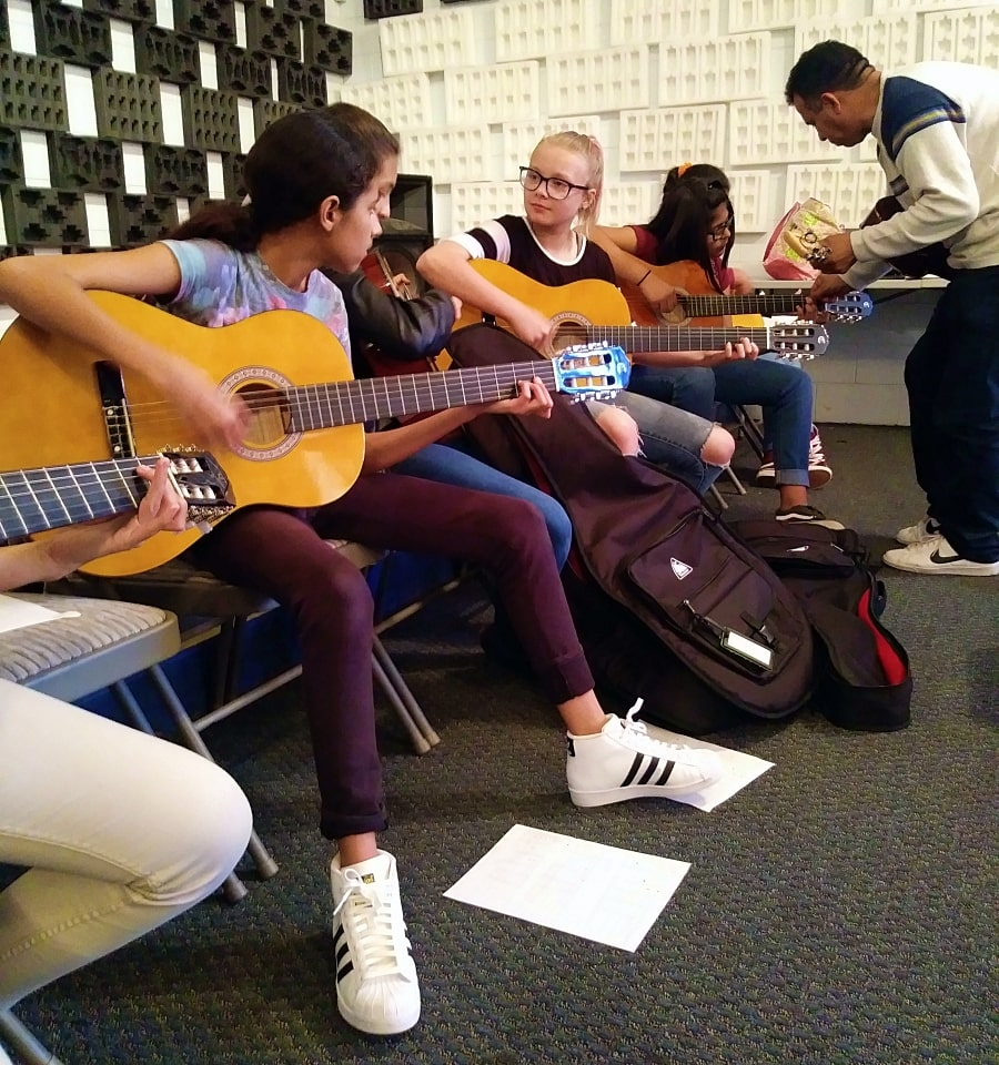 Young students sitting together for guitar lessons in San Benito County