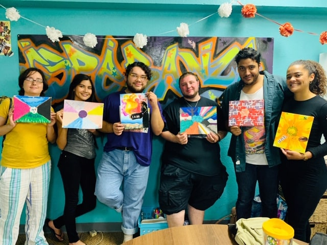 Group of artists standing together holding their finished creative projects
