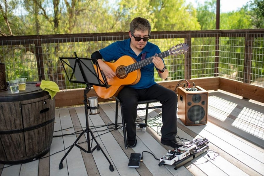 Guitarist sitting on porch playing music