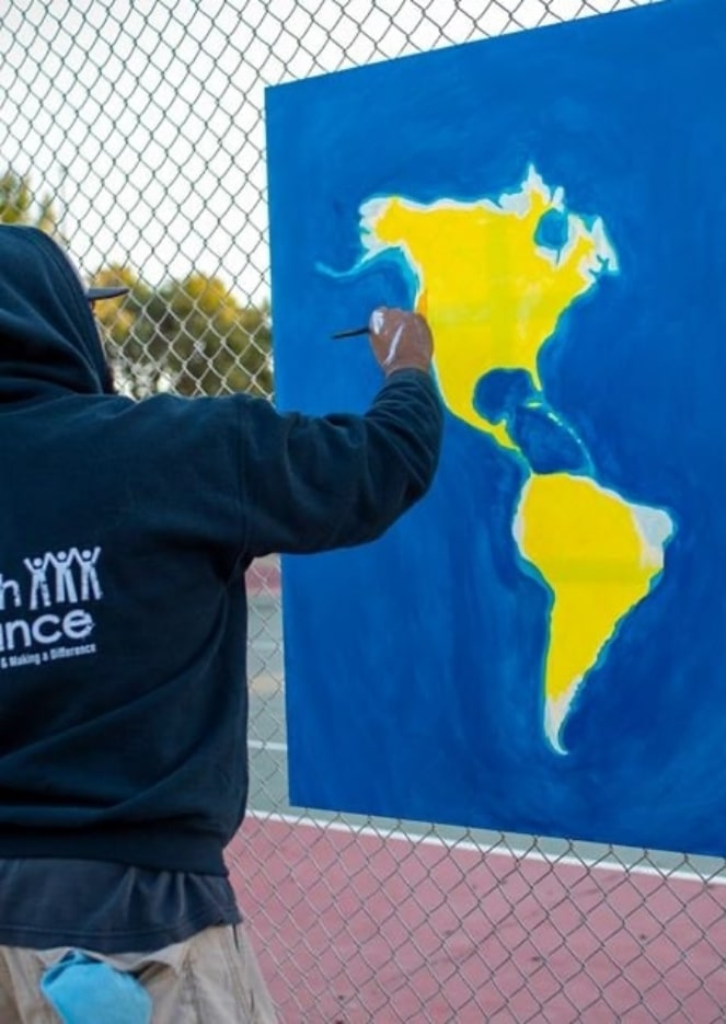 Artist painting continents North America and South America on canvas outdoors
