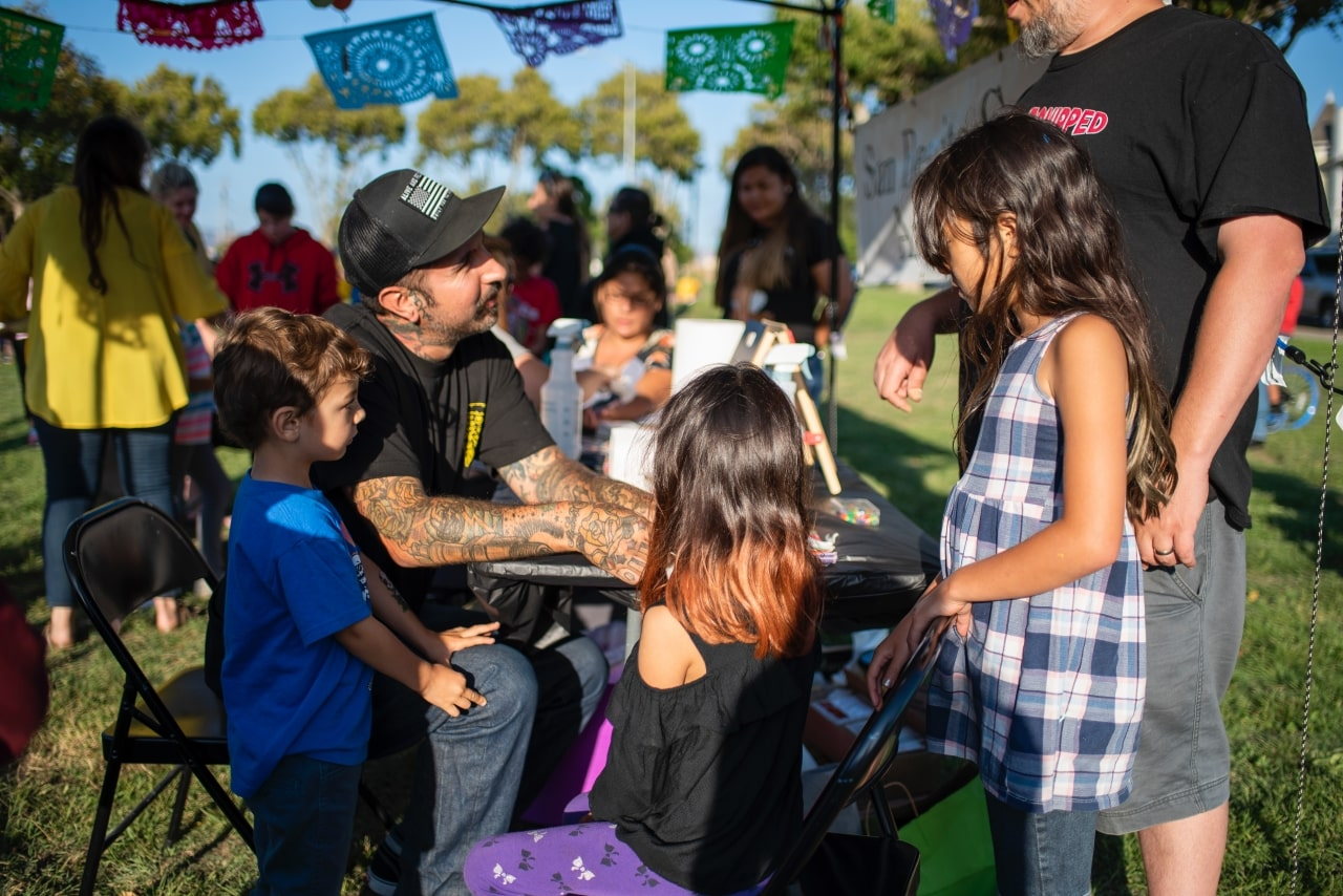Kids and man with tattoos involved in outdoor art exhibition at city park in Hollister, California